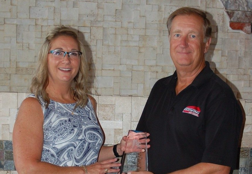 Red Wing Software President Ken Hilton receives a plaque from Brenda Duckworth, president of the Farm Financial Standards Council.